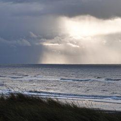 Licht scheint durch die Wolken auf das Meer