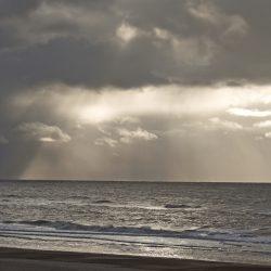Die Sonne bricht durch die Wolken über dem Meer