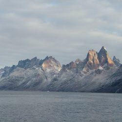 Steile Berge gehen über in graues Meer