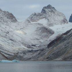 Kleiner Eisberg im Fjord vor Bergkette