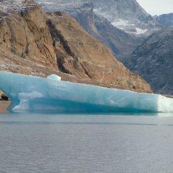 Türkisblauer Eisberg vor grauer Felswand