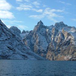 Blauer Himmel über zerklüfteten Bergen hinter kaltblauen Wasser
